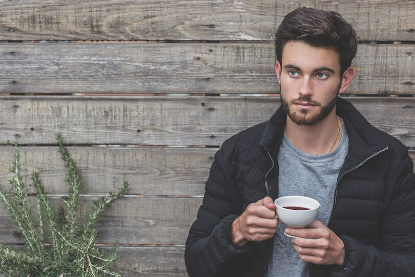 Young man drinking coffee by reclaimed wood wall for AIM Health men's health blog.