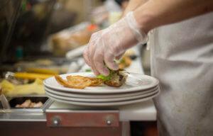 Food service worker preparing food